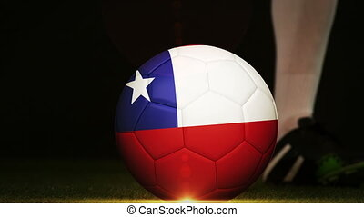 Football player kicking chile flag ball on black background