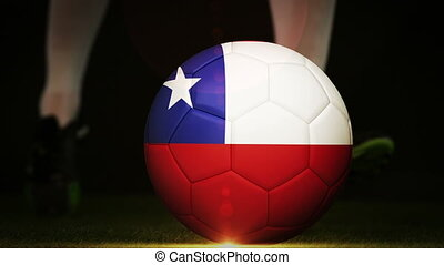 Football player kicking chile flag ball on black background in slow motion