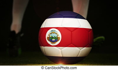 Football player kicking costa rica flag ball on black...