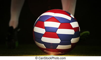Football player kicking dutch flag ball on black background...