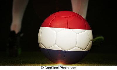 Football player kicking dutch flag ball on black background...