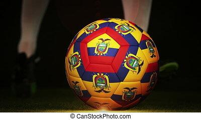 Football player kicking ecuador flag ball on black...