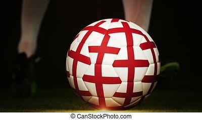 Football player kicking england flag ball on black...