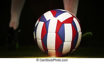 Football player kicking france flag ball on black background...