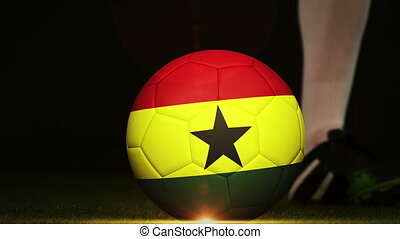 Football player kicking ghana flag ball on black background
