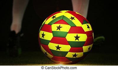 Football player kicking ghana flag ball on black background...