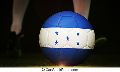 Football player kicking honduras flag ball on black...