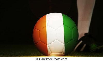 Football player kicking Ivory Coast flag ball