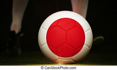 Football player kicking japan flag ball on black background...
