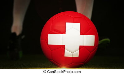 Football player kicking swiss flag