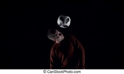 Football player making tricks with ball on head. Close-up....