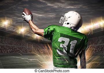 Football Player on a green uniform celebrating on a Stadium.