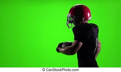 Football player running with the ball and a red helmet. Slow motion