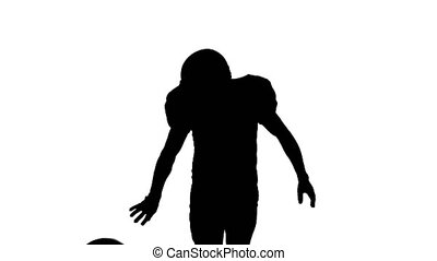 Football player running with the ball and throws it to the side. Silhouette. White background. Front view