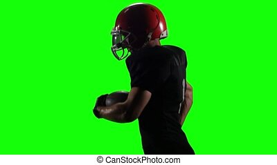 Football player running with the ball in his helmet and gear. Green screen