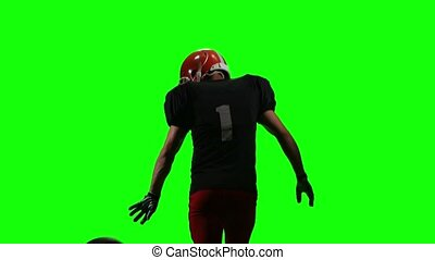 Football player running with the ball and throws it to the side. Green screen, back view