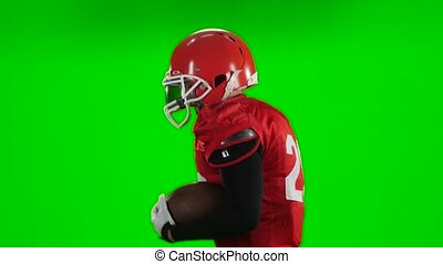 Football player starts with the ball in his hands. Green screen,close up