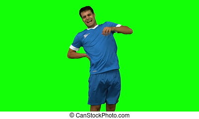 Football player suffering from back pain on green screen in...