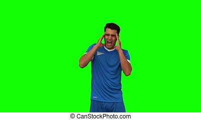 Football player suffering from headache on green screen in...