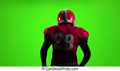 Football player touches the ball in his hand. Slow motion. Green screen