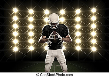 Football Player with a black uniform celebrating in front of...
