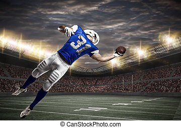 Football Player with a Blue uniform catching a ball on a...