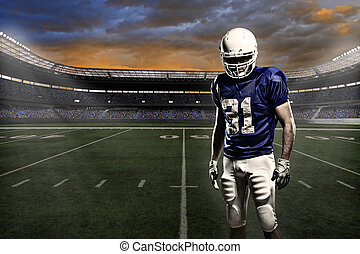 Football player with a blue uniform, in a stadium with fans ...