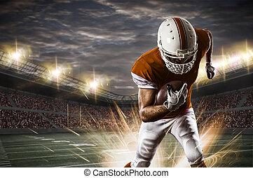Football Player with a orange uniform running on a stadium.