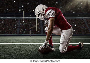 Football Player with a red uniform on his knees, on a ...