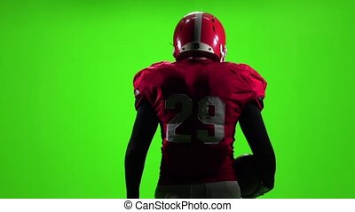 Football player with the ball is in the hands of. Slow motion. Green screen. Back view