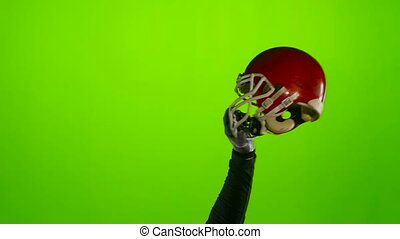 Football player's hand lifts the helmet. Green screen. Slow motion