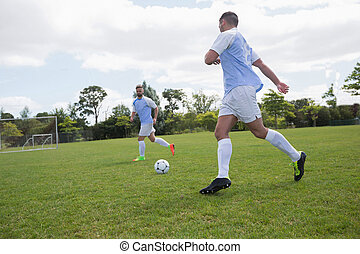 Football players playing soccer in the ground