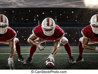 Football Players with a red uniform on the scrimmage line, ...