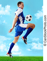Football - Portrait of soccer player jumping with ball on a ...