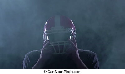 Football removes his helmet from his head in the smoke. Slow motion
