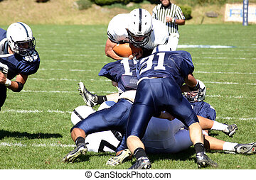 Football runningback being tackled