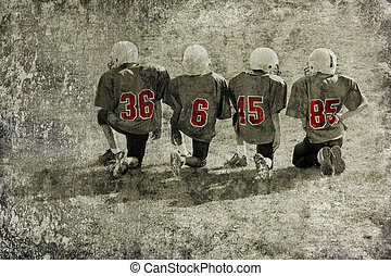 Football season - four football players are kneeling on the...