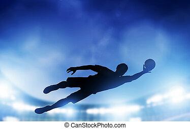 Football, soccer match. A goalkeeper jumping saving the ball from goal.