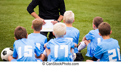 Football soccer match for children. Boys and coach sitting...