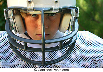 football - young boy in football uniform and helmet, his...
