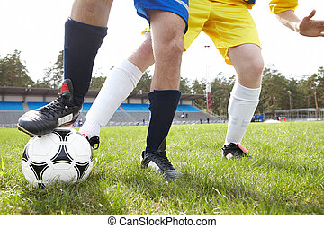 Football trick - Legs of footballer holding ball with ...