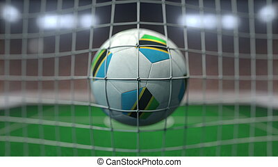 Football with flags of Tanzania hits goal net. 3D rendering
