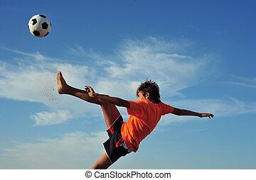 Young boy playing football - low angle virw