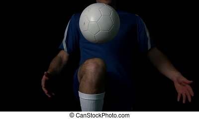 Footballer controlling the ball on black background in slow...