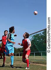 Footballer heading ball towards goal