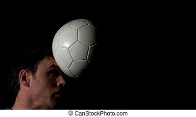 Footballer heading the ball on bla