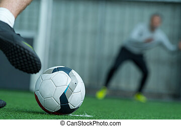 footballer is kicking ball into gate on field