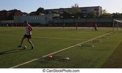 Footballer is running and kicking a soccer ball