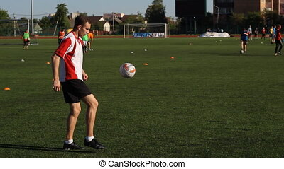 Footballer is training and bouncing a soccer ball on his leg
