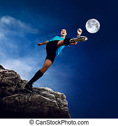 Footballer on the top of mountain at moon night